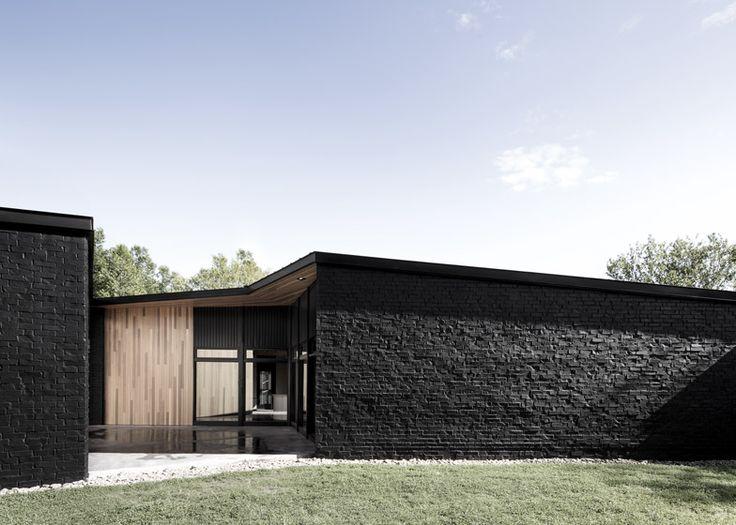 Sprawling house by Alain Carle contrasts black brick with warm cedar