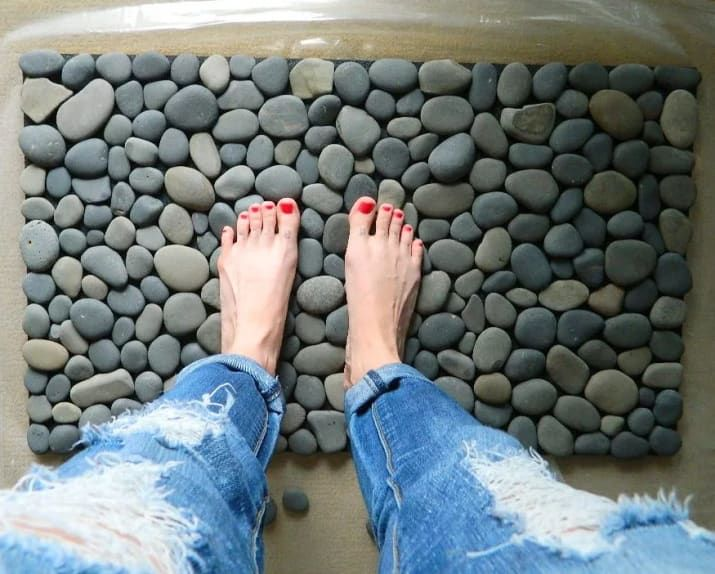 All you need is an outdoor rubber mat ($14.97 at Amazon), smooth stones ($17.20 for 20lbs. at Amazon), and waterproof silicone sealer ($4.28 at Amazon).Check out all the steps here.