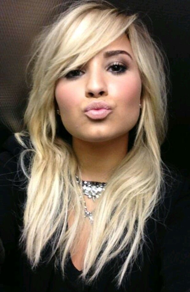Demi Lovato with long, blonde haircut with thick side-swept bangs.