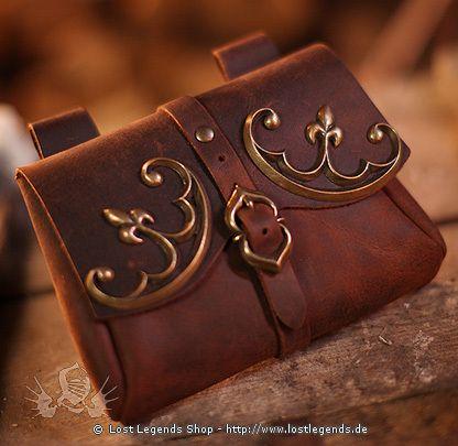 Diese schöne Gürteltasche aus samtweichem Nubukleder ist an historische Vorbilder des 12. bis 14. Jahrhunderts angelehnt. Eine mittelalterliche Schnallenreplik nach einem Originalfund prangt als Blickfang auf der Vorderseite und sorgt für sicheren Verschluss. Die beiden zeitgeössischen Beschläge sind typisch für die Epoche und geben der Tasche ein hochwertges und edles Aussehen. Die Abmessungen betragen 18 x 13 x 3 cm. Auf der Rückseite befinden sich zwei Lederschlaufen für Gürtel bis zu 6…