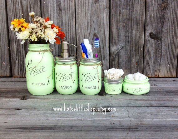 Add a little country charm to your home décor with this beautiful hand painted mason jar bathroom set. Each jar is painted by hand, distressed, sealed & tied with a cute bow. Giving it character and charm. Check out our shop reviews and sales for peace-of-mind in the product and service you will receive when purchasing from us. SET INCLUDES 1 Quart size mason jar vase 1 Pint size mason jar soap dispenser 1 Elite mason jar cotton ball or tissue holder 1 4oz. mason jar Q-TIP holder  ADD ON…