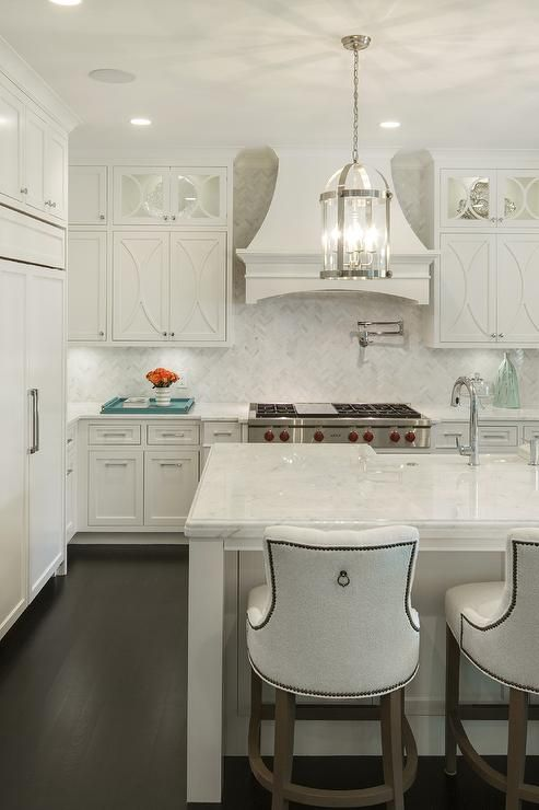 Off white kitchen features a pair of Round Edwardian Lanterns illuminating an off white kitchen island fitted with a sink and gooseneck faucet lined with off white nailhead counter stools by Baker.