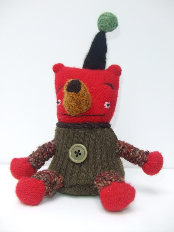 Nander is a special little teddy bear. He's red and teddy bears aren't usually that color so he gets a little down sometimes, that's why I gave him a black and green hat. He loves it. Nander can get quite chatty when he's had a few too many lemonades. He likes to sit in the sun. - (From the knitwit series, and the 'Land of Misfit Art'.  *_*)