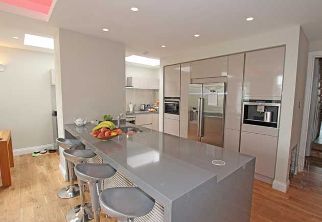This kitchen peninsula works wonderfully to integrate the extra wide structural pillar into the design so it is no longer conspicuous. The different heights within the peninsula ensure the worktop is at a suitable height for use but also enabled a breakfast bar to be incorporated, making the space both sociable and functional.