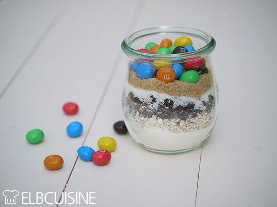 ELBCUISINE_Mini_Cookies_1 Mini-Cookie-Backmischung Für 1 Glas 10 Minuten Zubereitungszeit  Zutaten 25 g Mehl 1/4 TL Backpulver 1/4 TL Natron 25 g Haferflocken 15 g Schokoladentropfen oder geraspelte Schokolade 10 g brauner Zucker 10 g weißer Zucker ca. 15 g M&Ms bzw. das Glas einfach damit auffüllen  Verrühren mit 1 Ei, 20g Butter >>> vorher testen!!!, evtl weniger Butter Cookies mit 1TL auf Backblech setzen.