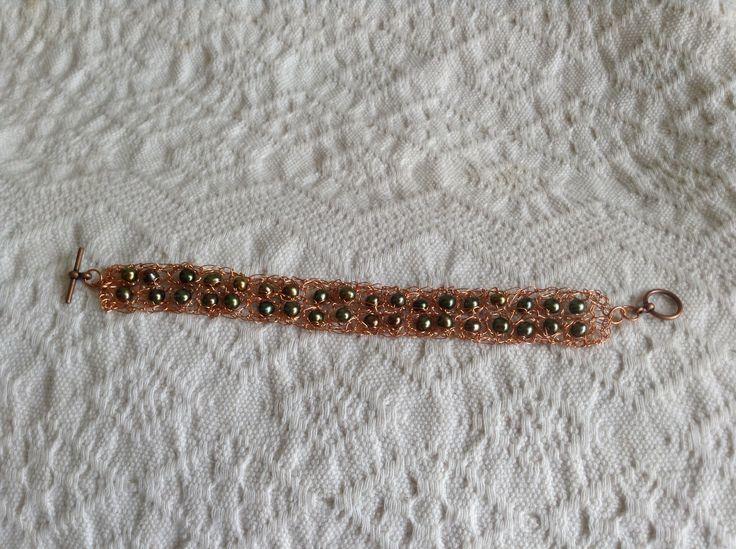Pulsera tejida a crochet con hilos de cobre y perlas.