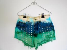 STEPS:  1. Purchase a pair of jeans from a thrift store and cut them into shorts.  2. Slightly distress the denim using scissors and a seam ripper.  3. Soak the top and bottom on the shorts in bleach.  4. Soak the bottom of the shorts in green dye.  5. Apply studs   6. What's up kewl pair of jortz?