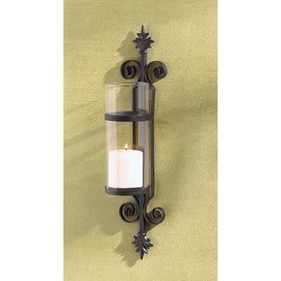 """Fleur De Les Candleholder. A palatial touch of Tuscan elegance adds old-world beauty to your home! Ornate matte-black forms a dramatic backdrop for a crystal-clear column of glass. Simply add your favorite color pillar candle for instant decorating magic! Metal with glass. Candle not included. 4 1/4"""" x 4 1/2"""" x 19 3/4"""" high."""
