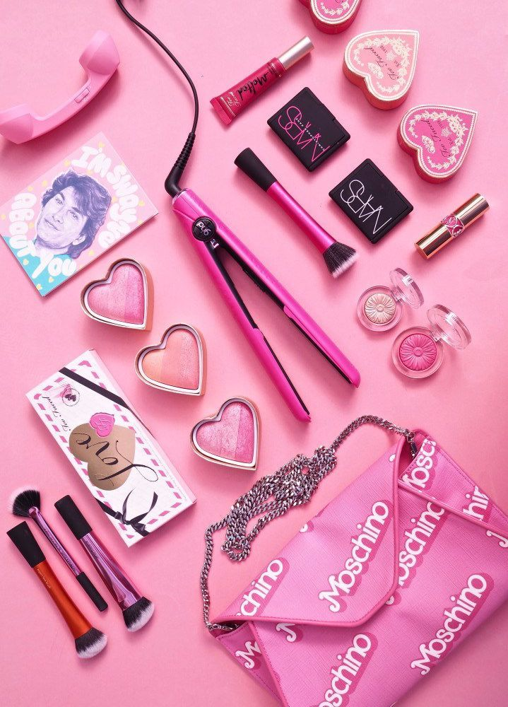 amazing pink flatlay filled with ghd straighteners and a moschino pink handbag! barbie and pink vibes.