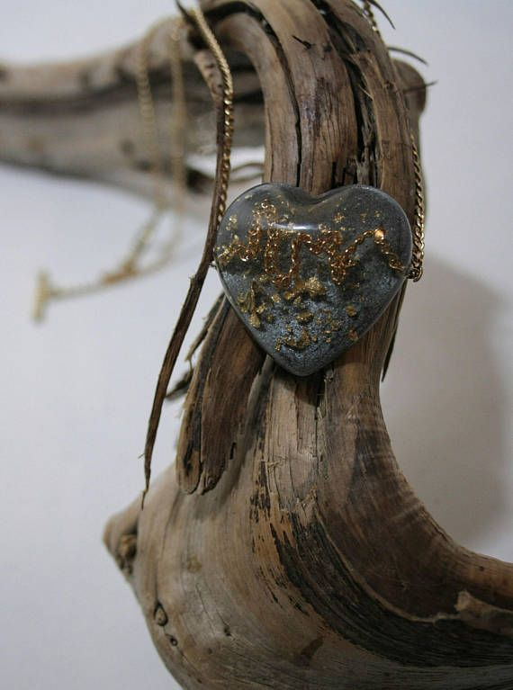 Heart pendant made of resin and embedded with gold chain in the lines of a heartbeat, and gold leaf. Backed with antiqued silver pearlex powder to make the heartbeat pop, this piece is one of a kind! All pieces are made one at a time and entirely by hand, embedded with locally