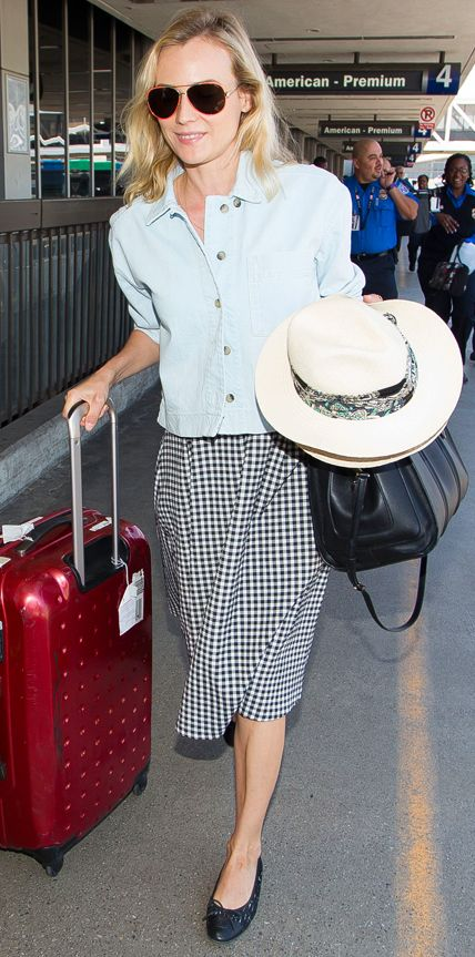 Diane Kruger nailed jet-setting style in a lightly washed denim jacket layered over a gingham print number. Aviators, a Lanvin straw hat (in her grip), a black carryall, and ballet flats rounded out her look.