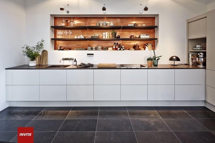 Det stilrene Athena-køkken får et varmt twist med den oplyste kobberbeklædning bag hylderne.