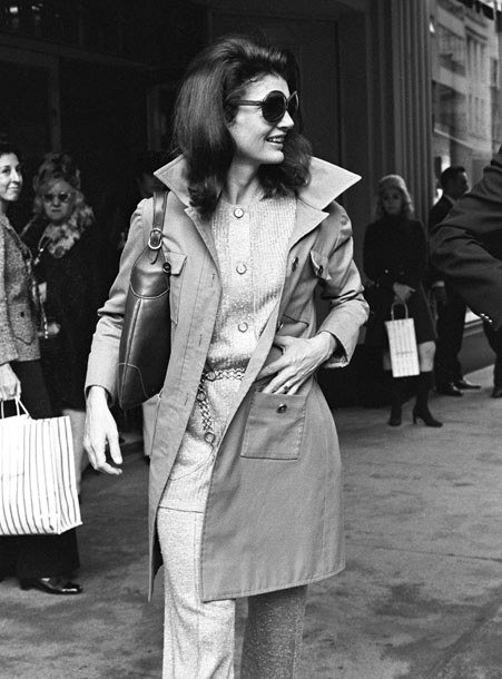 Jackie Onassis is tres chic in this casually glam outfit. the trench, signature sunglasses, and chain belt are timeless accessories that prove the sun never sets on cool.