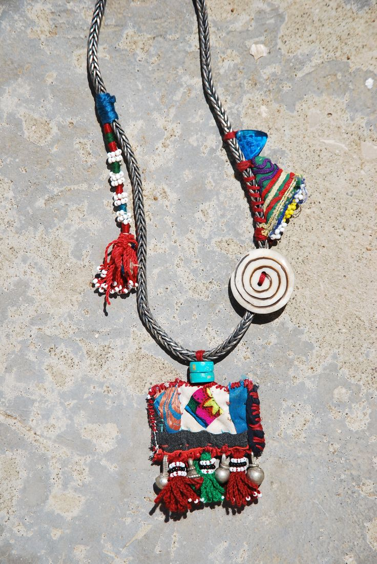 Kinship Stories: Tribal art necklace whose base is made of a  sterling silver chain from Nepal (925k). Dangling are turquoise beads and a piece of Turkoman applique. It comes from an old baby's hat. Attached to it are Egyptian tassels and Yemeni mixed silver beads (30k). The larger Uzbek tassel comes from an old wall hanging. The button is made of yak horns (bulls from the Himalayas). The two triangles are protective Afghani amulets. The necklace is a handmade, one-of-a-kind piece.