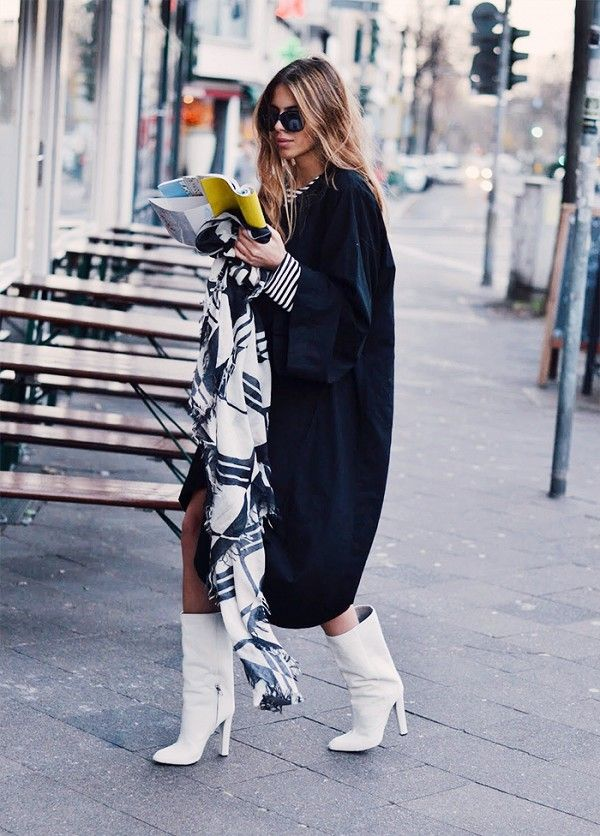 Maja Wyh wears a black cocoon coat, striped top, plaid scarf, and white boots
