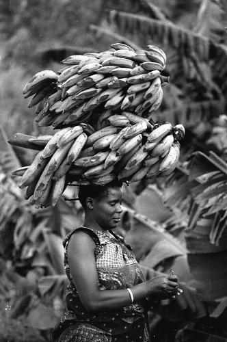 Africa |Woman carrying bunches of bananas, Bunia, Congo (Democratic Republic) |©Eliot Elisofon. 1970