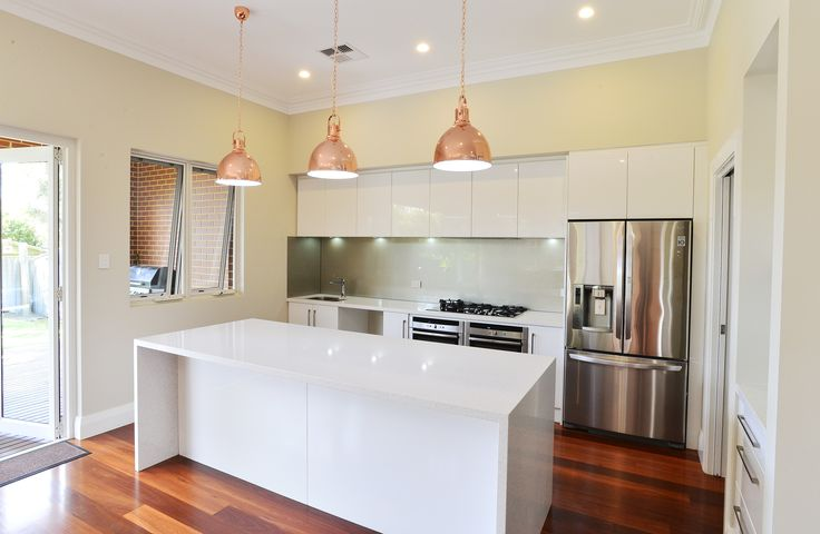Stunning new kitchen in classic white, with stainless steel appliances, glass splashback, feature lighting over the breakfast bar, all offset beautifully against the natural beauty of the polished jarrah floorboards. #homerenovation #perth #newkitchen #homeaddition #characterhome