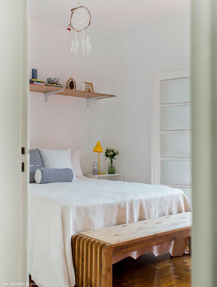 Quarto de casal tem cores claras e móveis de madeira como a prateleira suspensa.