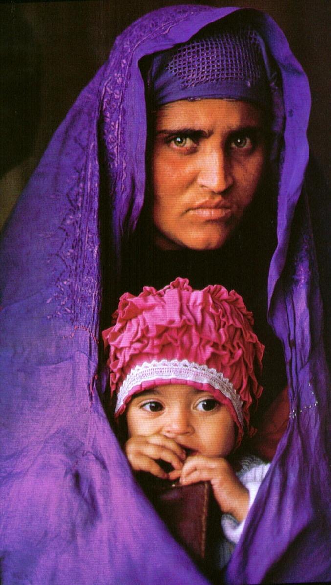 """Sharbat Gula tinha 12 anos quando foi fotografada durante uma reportagem da """"National Geographic"""" sobre a ocupação soviética no Afeganistão. Se tornou uma das fotografias mais conhecidas do mundo. Em 2002, o fotógrafo Steve McCurry, autor da fotografia, reencontrou Gula, então, com 30 anos, numa região remota do Afeganistão. Ela não tinha a menor ideia do impacto que sua foto causou na civilização ocidental."""