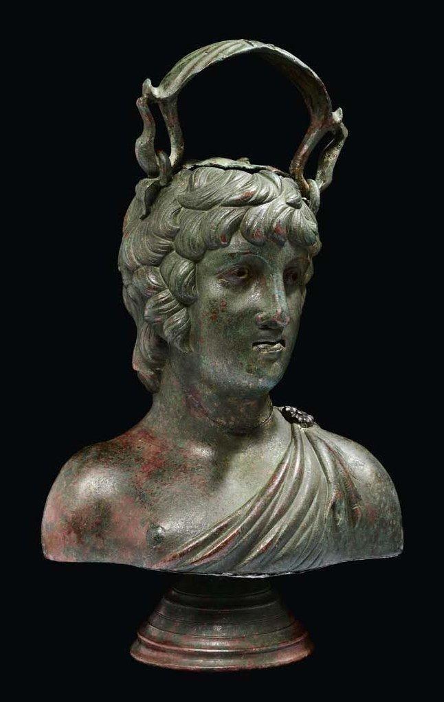 """Balsamaire au """"buste d'Antinoüs"""". Grand balsamaire plastique représentant probablement le buste d'Antinoüs reposant sur un piédouche. Il est torse nu, en partie couvert par une dépouille de caprin agrafée… - Pierre Bergé & associés - 01/06/2012"""
