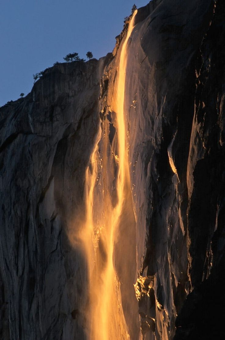 """Horsetail Fall at Sunset by Michael Frye via npr: 'The waterfall is perched high on an open cliff where it can catch light from the sunset — but not just any sunset. """"It's this brief window of light around the third week of February where the sun sets at just the right angle to light Horsetail Fall just as it's sinking,"""" Frye says.' #Photography #Yosemite #Horsetail_Fall  #Sunset"""