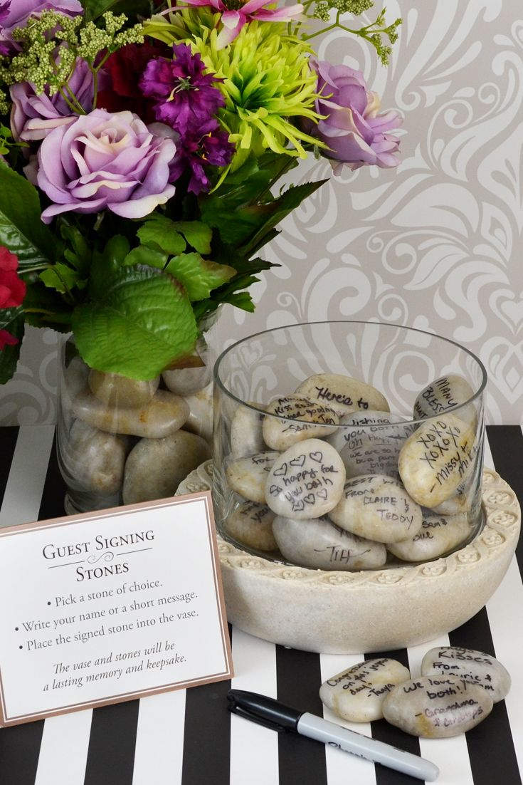 Signature stones are a new and popular alternative to traditional wedding guest signature books. Guests sign in on a real stone with a felt-tip pen or marker and place them in a vase or bowl like this one. The signature stones and vase or bowl can then be displayed as a decorative conversation piece in the newlywed couple's home.