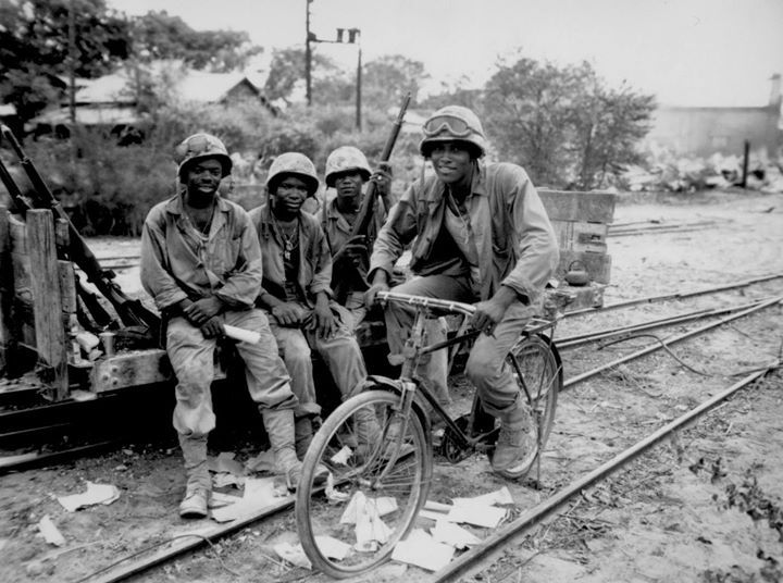 American men of the US Marine Corps Third Ammunitions Company at Saipan Mariana Islands June 1944. Private First Class Boykin on bicycle and Privates First Class Anthony Shackelford and Purdy sitting.