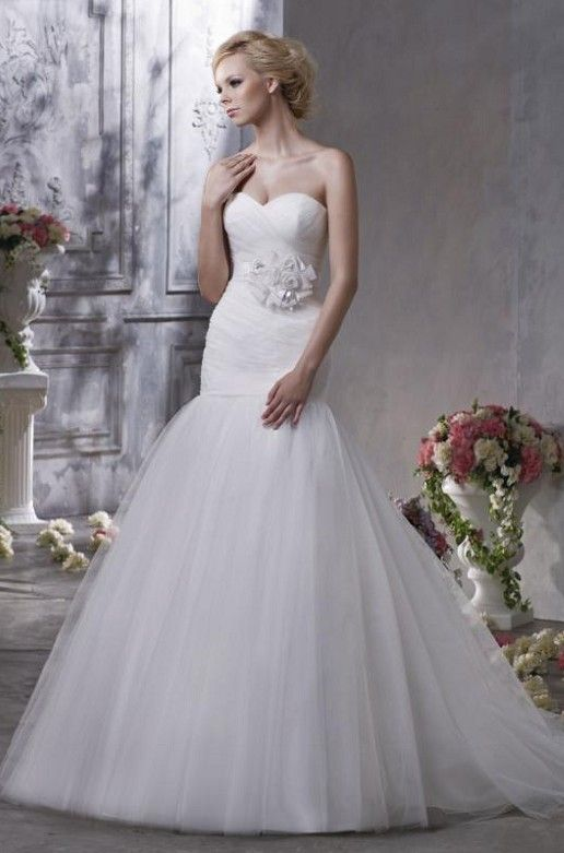 Mermaid style wedding dress with tulle bottom, with sweetheart top, and flower detail at natural waist.