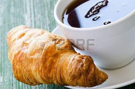 Кофе и круассан на деревянный зеленый стол photo