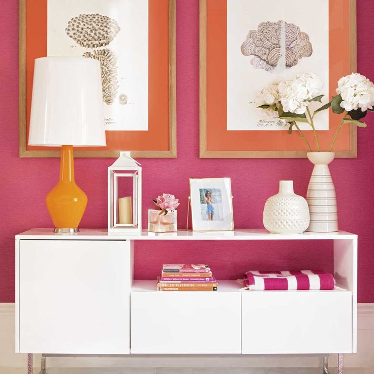 Looking for hallway design ideas? Be inspired by this hot pink and orange hall with white furniture and framed artwork