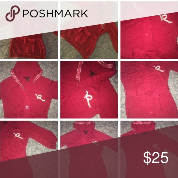 """🎊ROCAWEAR Button Hooded Sweater ROCAWEAR Button Down Hooded Sweater Size:  Medium Color:  Red with Silver Condition:  Pre-Owned;  Very good condition!  Talk about style!!  Looks great with jeans and leggings!!  ~  Hood lined on the inside with logo """"R"""" in sparkly silver ~  3/4 Sleeves ~  Big Buttons Closure Front ~  Rocawear """"R"""" logo in the front left in sparkly silver ~  Waist tie   Measurements  Armpit to Armpit:  21"""" Waist (measured on elastic waistband): 20"""" Length (from shoulder…"""