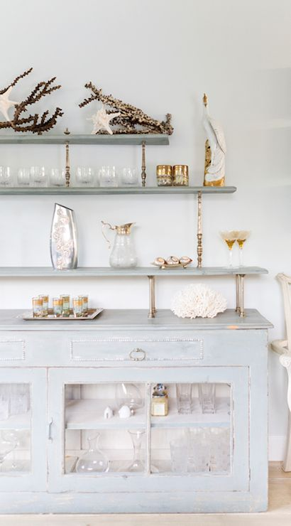 Pretty dining room with distressed blue buffet with glass doors paired with customized staggered gray shelves supported by brass rods accented with vintage glassware, a silver vase, coral branches and starfish.