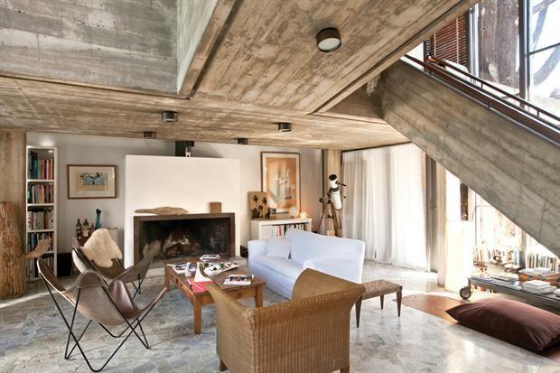 Mesa baja con ruedas 'Vico Magistretti' (Gris Dimensión), alrededor de una mesa de madera, sillas BKF originales, una con un cuerito de oveja (Mercado de Frutos), sillón de ratán (Desde Asia).  Foto:Living /Archivo LIVING
