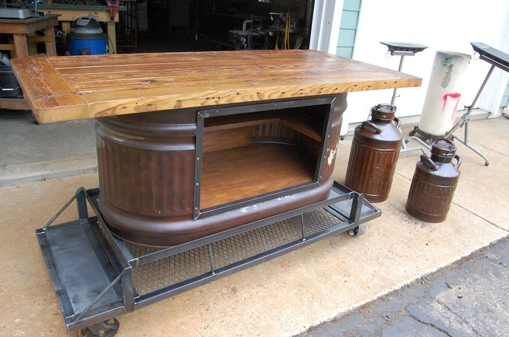 Kitchen Island or table made from a vintage livestock water tank, reclaimed barn wood on cast iron casters.