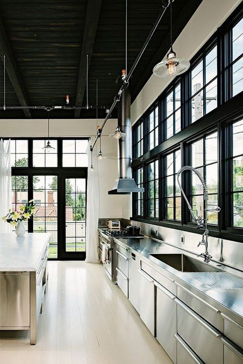 Sleek and modern #kitchen with #dark ceilings, black window borders & stainless steel counters!