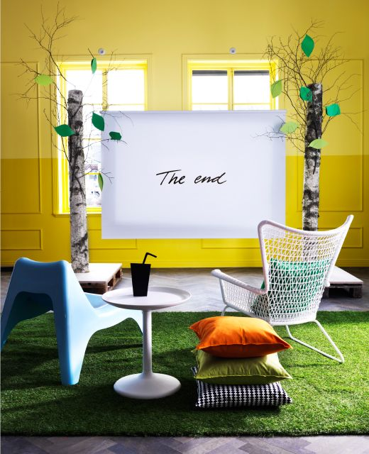 A roller-blind is hung between two trees with two outdoor chairs and a small table facing it.