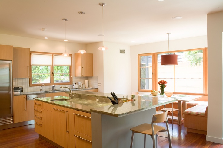 The expansive kitchen with built-in breakfast table and bar seating flows into the den.