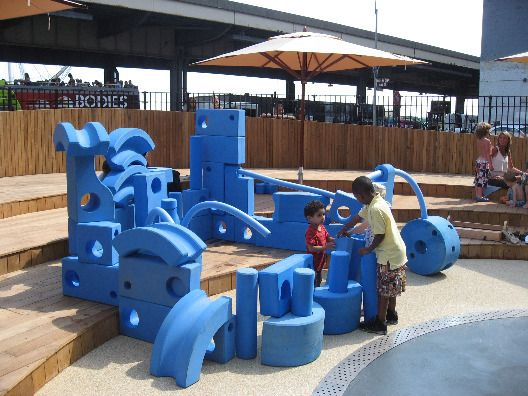 Blue foam building blocks allow kids to create structures and interact with other children at the Imagination Playground