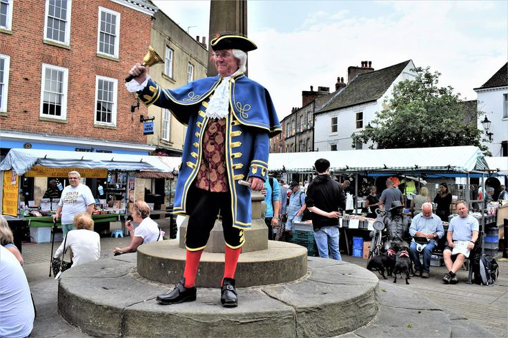 """This is Roger Hewitt the """"Town Crier"""" in Knaresborough, North Yorkshire, England on market day.   He rings the bell to attract everyone's attention and reads from his manuscript describing a host of event or attractions in Knaresborough. (11am, 12pm and 1pm)  To the right we have three men sat on the bench but the one on the left of them in a statue of John Metcalf better known as BLIND JACK a famous son of Knaresborough  Jack was the first professional road builder to emerge du..."""