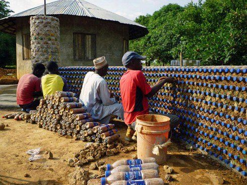 "RECYCLED PLASTIC BOTTLE HOUSE BUILT IN NIGERIA - Stronger Than Conventional Construction - The bottles are actually filled with dry soil or construction waste, not sand (an ""unnecessary expense""), said John Haley of ECOTEC, the firm that is training local masons in the technique. They are then laid in rows like bricks and bound together with mud, producing a sturdy, well-insulated, and inexpensive three-room structure that is resistant to both bullets and earthquakes."