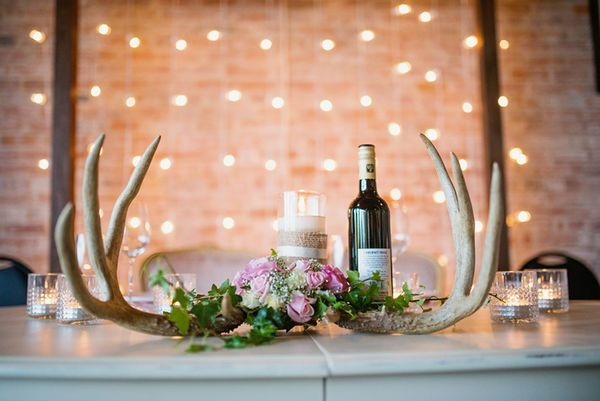 Faux antlers, string lights and a rose centerpiece make lovely table decor for a fall wedding.