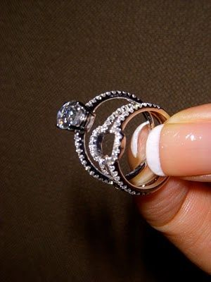 Wedding ring where your engagement ring slips in between two bands. Love this, clean way to get the three band