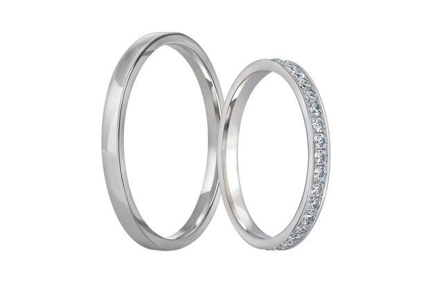 Jemné snubní prstýnky s rovným profilem a celolesklým povrchem. Dámský kroužek je doplněn kameny fasovanými po celém svém obvodu.