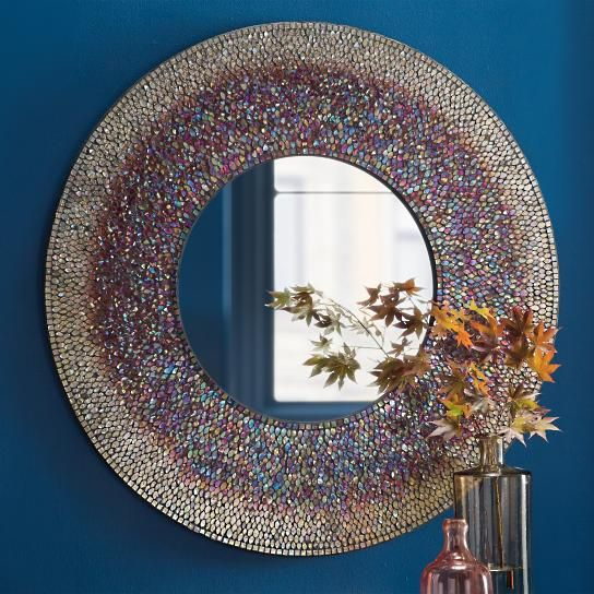 Our Solange Mirror is a more sculptural modern accent. The round mosaic composition frame makes a statement with colors of smoky quartz, and fire-opal    orange, complemented with beautiful blues, greens, and touches of purple. At 36 in diameter, this mirror has the presence of an artwork piece, and will    looking amazing in any room.            Beautiful round wall mirror with a mosaic-style frame                Complements any space                Frame colors include smoky quartz, fir...