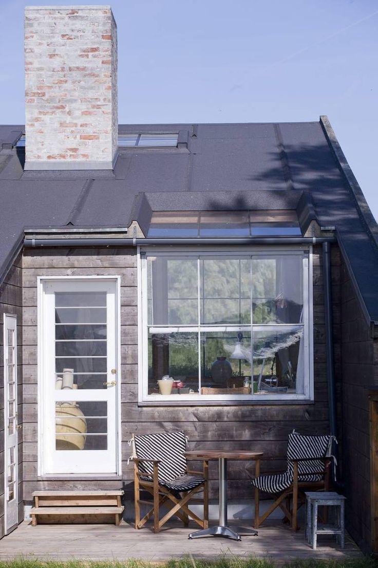 LAV TERRASSE: Terrassen ligger nede på terrenget, og dermed lavere enn gulvnivået i stuen. Det gjør at hagemøblene under vinduet ikke kommer i veien for utsikten innenfra. Hytta er tegnet og bygget av en båtbygger. Utvendig kledning er Douglasgran, taket er svart takpapp.