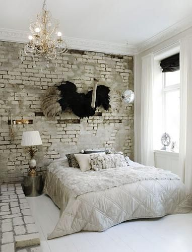 The partially covered brick wall, delicate chandelier and grey hues, lend perfectly to this ostrich headboard. #animalistic