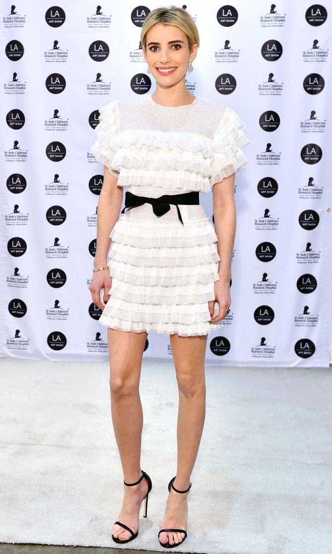 Emma Robers in a white ruffle mini dress