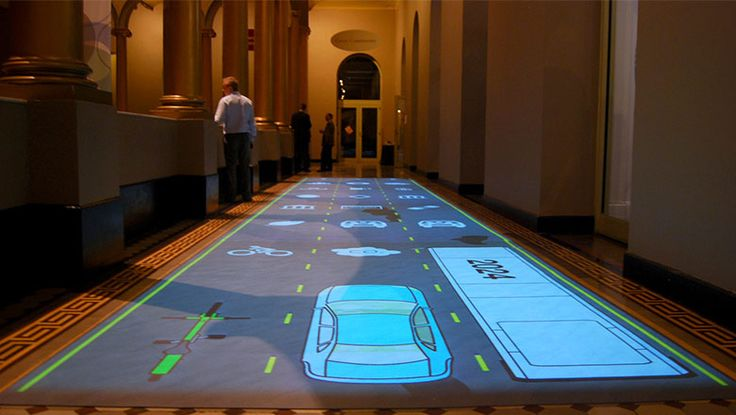 """Using full-body interaction rarely achieved through screen-based installations, Potion created the """"Transportation Hallway"""" for the National Building Museum's Green Community exhibit showcasing sustainability. """"Transportation Hallway"""" features three human-scale """"traffic lanes""""—bicycle, car or bus—projected onto the floor. As visitors navigate each lane, their chosen mode of transport moves with them while pop-up signs describe that vehicle's benefits and consequences to the environment."""