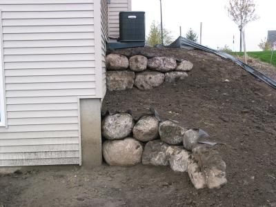 Rock retaining wall for north side of house.  (note the a/c unit.)