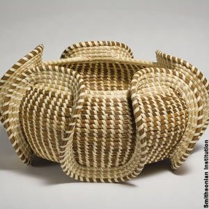 """Sweergrass is native to the coastal dunes of the Carolinas, and it provided an ideal material for African slaves to produce a tightly woven coiled basket. Today's virtuoso Lowcountry basket makers often create ingenious designs such as the above """"wave"""" basket made with sweetgrass and bulrush sewn with palmetto."""